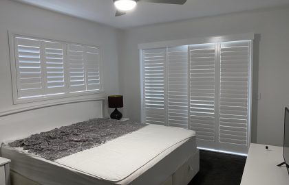 white shutters window and sliding door in bedroom at cooroy